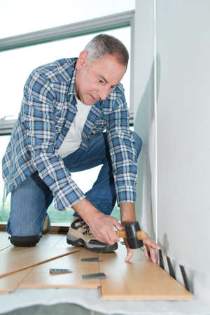 carpenter installing new laminated wooden floor at home Stock Photo