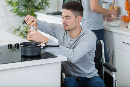disabled young man in wheelchair is cooking in the kitchen
