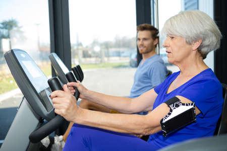 persistence: senior woman on the exercise machine