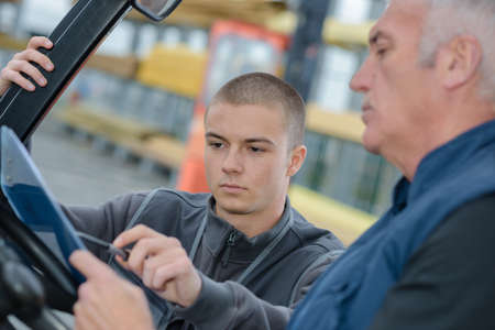 construction vehicle: instructor teaching apprentice how to drive a heavy construction vehicle Stock Photo