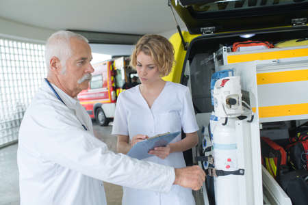 casualty: doctor and paramedic or ambulance team reviewing gear at hq Stock Photo
