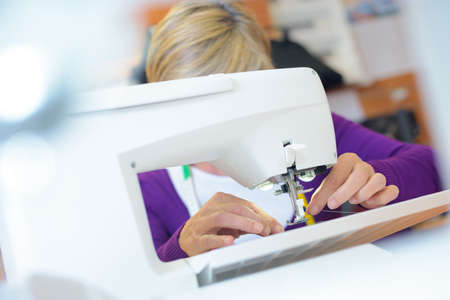 woman putting a thread in a sewing machine