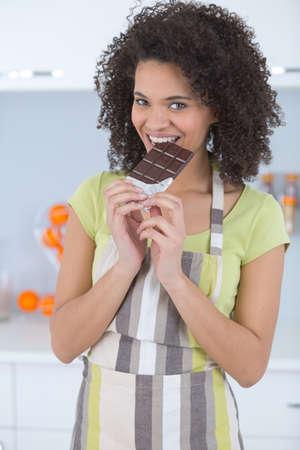 明るい背景にチョコレートを食べる若い女性 写真素材