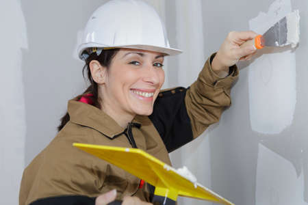 female plasterer doing a wall renovation with spatula and plaster