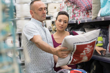 sopping couple choosing cloths at home decoration store