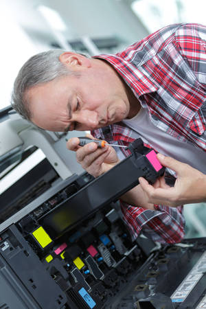 information equipment: male tech trying to repair the office printer