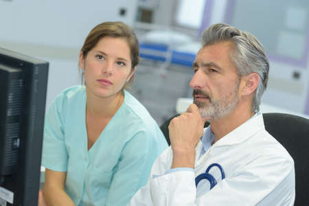 handsome doctor talking to pretty nurse about patients case