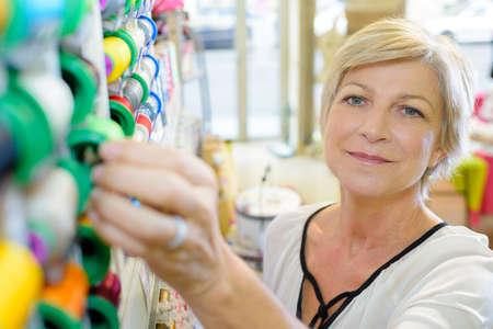happy mature woman customer picking various cotton stitching spools Stock Photo