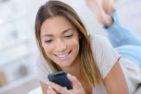 young smile woman reading smart phone on bed