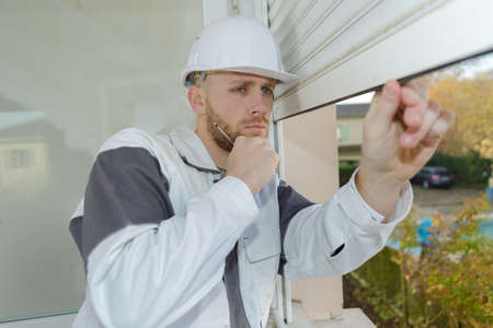 toolroom: worker inspecting pvc profiles and windows with shutter