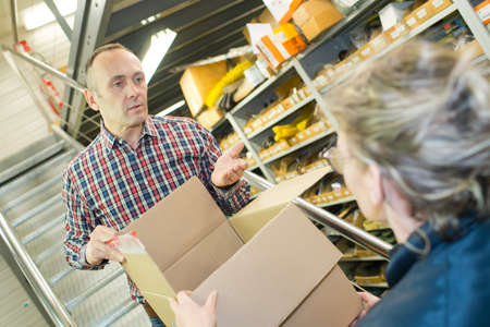 fruit trade: young seller in supermarket with senior client Stock Photo