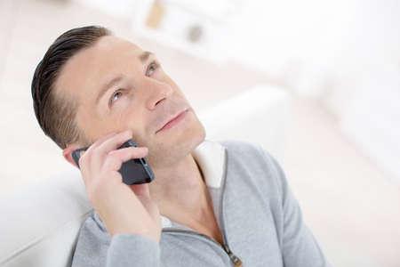 man in sofa talking on phone