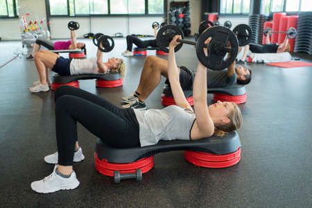 group of people carring out exercise with a bar Stock Photo