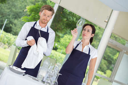 female and male bartender drying wine glasses Stock Photo