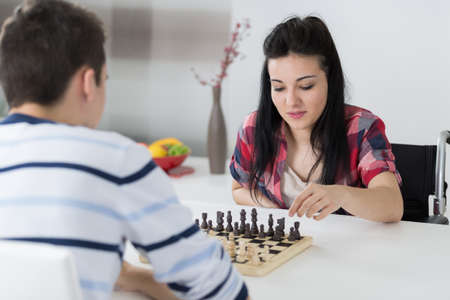 love strategy: young couple playing chess indoor Stock Photo