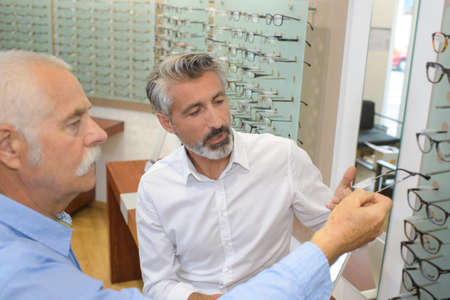 matching: ophthalmologist and male pensioner choosing glasses in optics store