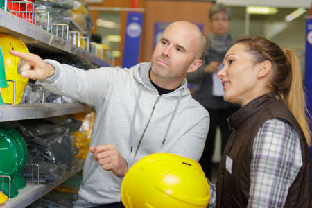 workers choosing construction helmets in hardware store Stock Photo