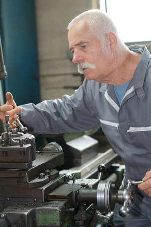metalic: senior metal worker using machine in workshop Stock Photo