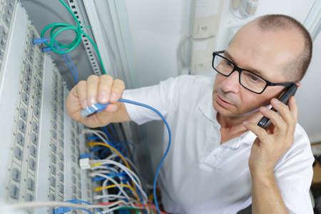 man met elektrische kabel met mobiele telefoon om hulp vragen Stockfoto