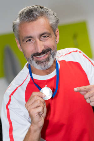 man holding a gold medal winner in a competition Stock Photo