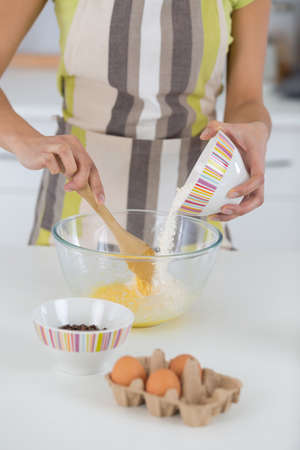 woman is mixing eggs in a bowl