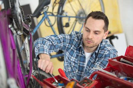 man repairing bike in his workshop