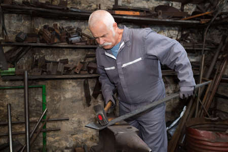 senior blacksmith forging the metal Stock Photo