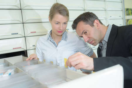 Man and pharmacist looking into drawer Stock Photo