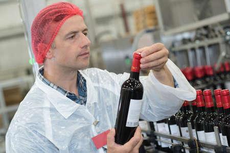 volwassen mannetje bedrijf nieuw geproduceerde fles wijn Stockfoto