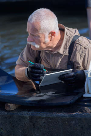 niloticus: senior fish farm manager writing on clipboard Stock Photo