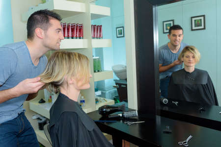 hairtician: male hairstylist is making a haircut for a happy woman