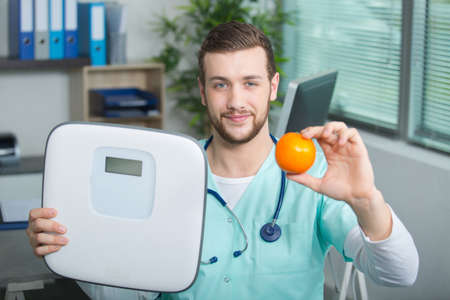 nurse holding fruit and weighing scale