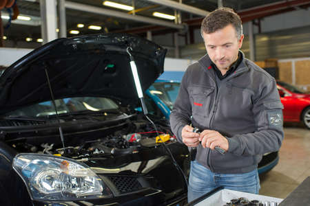 car mechanic working with tool in service workshop