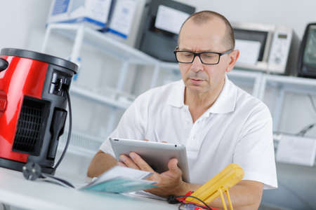 daily room: portrait of professional repairman gathering informations on internet