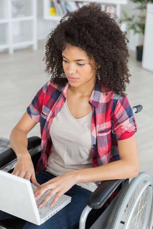 impaired: young girl on wheelchair surfing web