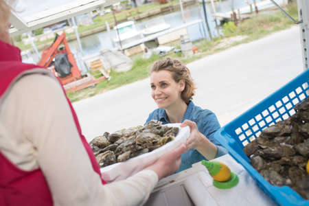 positive female shop assistant selling fresh fish and chilled seafood Stock Photo