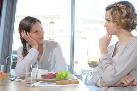 co: two female students are eating together at the restaurant chatting