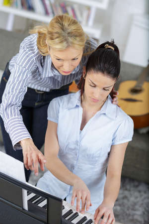 young woman in lesson with piano teacher Stock Photo