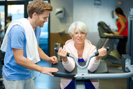 female senior in the gym assisted by the trainer