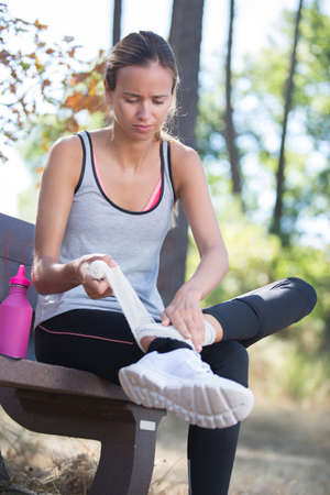 warming up: young woman with injured knee or leg outdoors