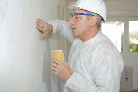 sanding block: senior builder sanding the wall with a sanding sponge Stock Photo
