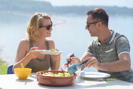 poblíž: couple eating a salad on a terrace near the sea