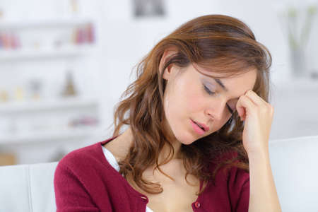 woman sitting on couch suffering from head pain