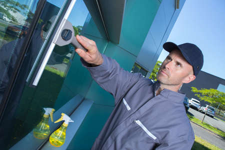 groundskeeper: professional cleaner swiping window on site Stock Photo