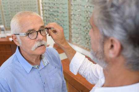 matching: senior man trying spectacles frames at optician Stock Photo