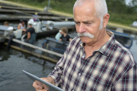 experiencing: shellfish or fish farm manager ordering supplies on his tablet
