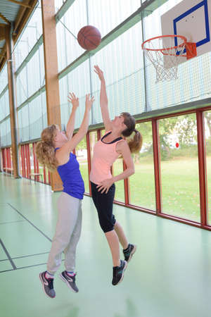 Female basketball players midair