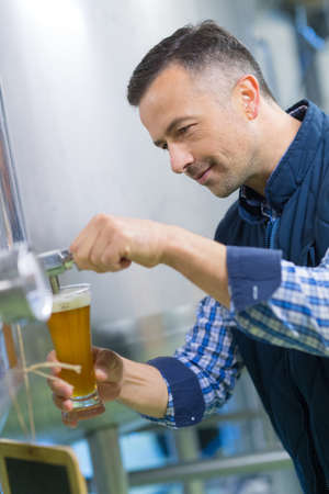 attentive: brewer testing beer at brewery