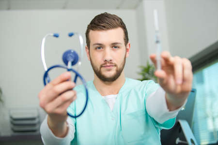 doctor holding stethoscope and syringe Stock Photo