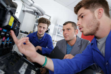 two apprentices and teacher working on printer